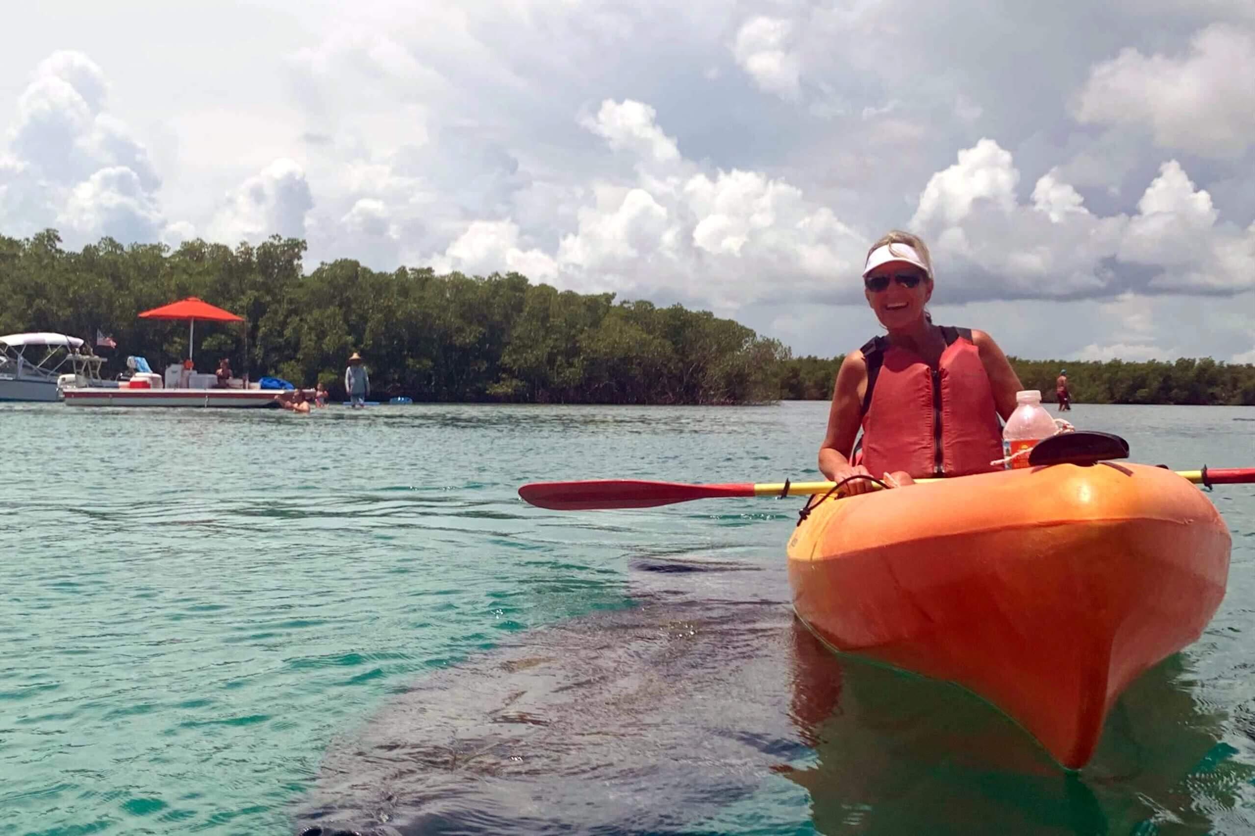 Babette enjoying a kayaking adventure while a manatee swims up close...